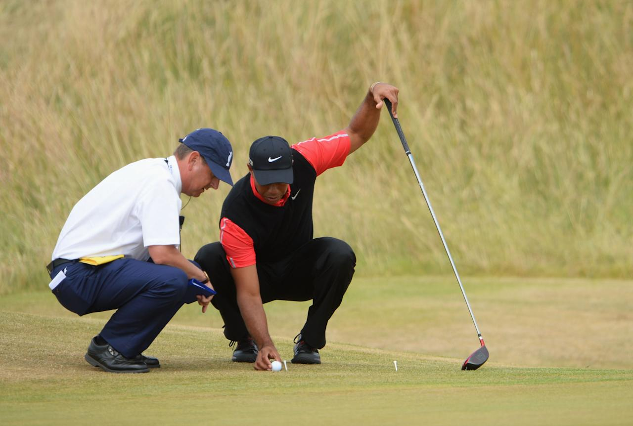 GULLANE, SCOTLAND - JULY 21: Tiger Woods of the United States works with a rules official after a drop during the final round of the 142nd Open Championship at Muirfield on July 21, 2013 in Gullane, Scotland. (Photo by Stuart Franklin/Getty Images)