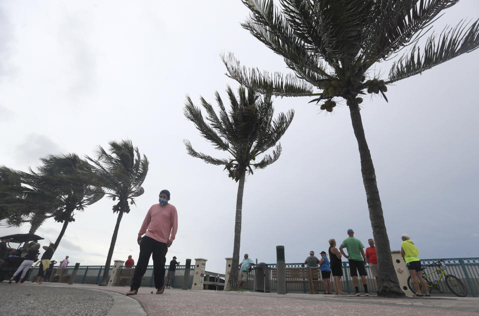 People gather to watch the strong waves on the beach as palm trees sway in the wind, Sunday, Aug. 2, 2020, in Vero Beach, Fla. Isaias weakened from a hurricane to a tropical storm late Saturday afternoon, but was still expected to bring heavy rain and flooding as it barrels toward Florida. (AP Photo/Wilfredo Lee)