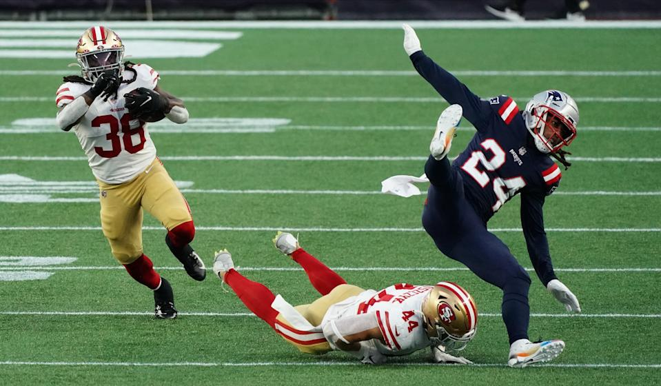 Oct 25, 2020; Foxborough, Massachusetts, USA; San Francisco 49ers running back JaMycal Hasty (38) runs the ball with help from fullback Kyle Juszczyk (44) against New England Patriots cornerback Stephon Gilmore (24) in the first half at Gillette Stadium. Mandatory Credit: David Butler II-USA TODAY Sports