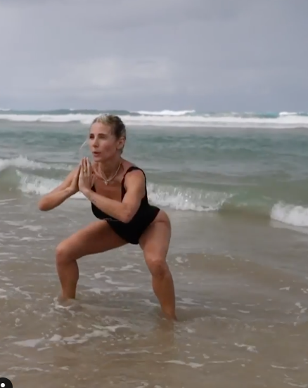 A photo of Elsa Pataky wearing a black swimsuit doing squats in the shallow water at the beach.