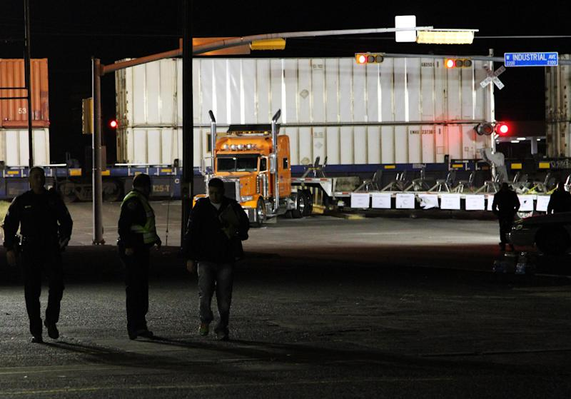 Police officers walk in front of a trailer that was carrying wounded veterans in a parade when it was struck by a train in Midland, Texas, Thursday, Nov. 15, 2012.  Four veterans were killed and 16 other people were injured when the train slammed into a parade float carrying the returning veterans to a banquet to honor them officials said Friday. The float took the full force of the train at a railroad crossing Thursday afternoon. Some people managed to jump clear as the train, with its horn blasting, bore down on the float decorated with American flags.  (AP Photo/Juan Carlos Llorca)