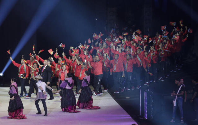 Timor Leste team hold flags during the opening ceremony of the 30th South East Asian Games at the Philippine Arena, Bulacan province, northern Philippines on Saturday, Nov. 30, 2019. (AP Photo/Aaron Favila)