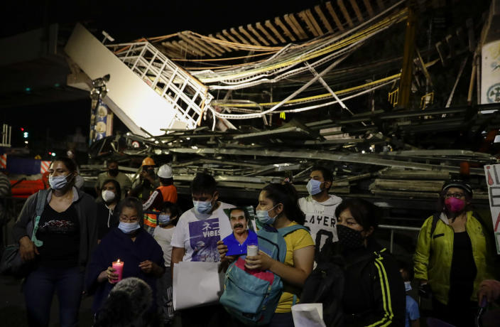 Family members protest demanding justice for the people who died in Monday's subway collapse, at the site of the wreckage in Mexico City's south side, Friday, May 7, 2021. An elevated section of Line 12 collapsed late Monday killing at least 25 people and injuring more than 70, city officials said. (AP Photo/Eduardo Verdugo)