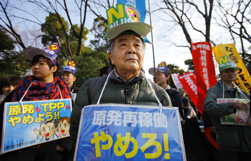 """Protesters stage an anti-nuclear plant demonstration outside the national diet building in Tokyo, Sunday, March 9, 2014. Participants at the demonstration, planned across cities in Japan, said they would never forget the March 11, 2011, nuclear disaster, the worst since Chernobyl. The placard, center, reads: """"No to restart nuclear reactors!."""" (AP Photo/Junji Kurokawa)"""