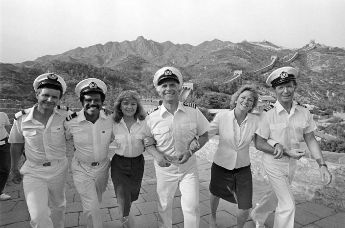 """FILE - In this May 30, 1983 file photo the cast of the television series """"The Love Boat,"""" at the Great Wall near Beijing, China. From left to right: Fred Grandy, Ted Lange, Jill Whalen, Gavin MacLeod, Lauren Tewes and Bernie Kopell. Gavin MacLeod has died. His nephew told the trade paper Variety that MacLeod died early Saturday, May 29, 2021. (AP Photo/Liu Heung Shing, File)"""