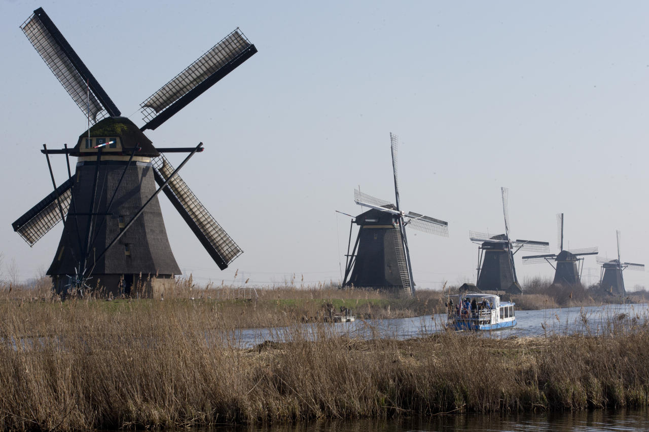 FILE - In this Feb. 14, 2017, file photo, tourists on a boat tour windmills lining Hooge Boezem van de Overwaard canal at the Unesco World Heritage site in Kinderdijk, Netherlands. (AP Photo/Peter Dejong, File)