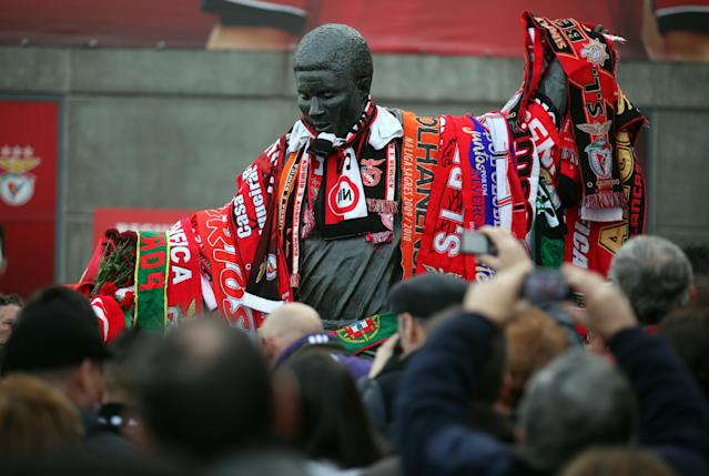 People gather around the sculpture of the Portuguese soccer player legend Eusebio covered by scarfs, at the Benfica's Luz stadium in Lisbon, Sunday, Jan. 5, 2014. Eusebio, the Portuguese football star who was born into poverty in Africa but became an international sporting icon and was voted one of the 10 best players of all time, has died aged 71, his longtime club Benfica said. (AP Photo/Francisco Seco)