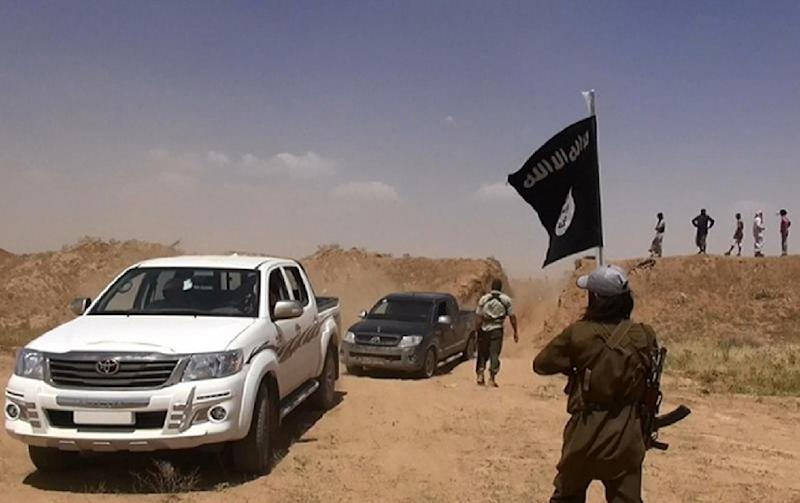 An image made available by the jihadist Twitter account Al-Baraka news on June 11, 2014 allegedly shows a militant of the Islamic State group waving the Islamic jihad flag as vehicles drive between Iraq's Nineveh province and Al-Hasakah, Syria (AFP Photo/)