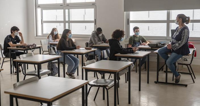 "High school students and their teacher in Cascais, Portugal, wear masks on their first day back in school on May 18. <span class=""copyright"">(Horacio Villalobos / Corbis via Getty Images)</span>"