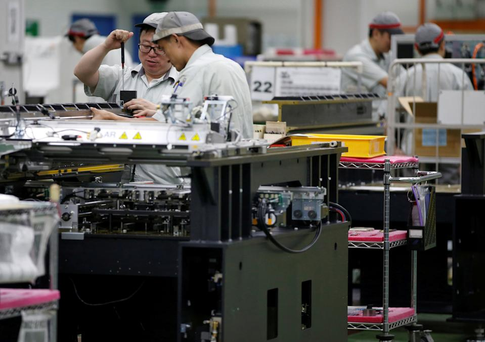 Employees are seen by their workstations at a printed circuit board assembly factory in Singapore June 28, 2016. REUTERS/Edgar Su/File Photo                   GLOBAL BUSINESS WEEK AHEAD PACKAGE - SEARCH BUSINESS WEEK AHEAD SEPTEMBER 26 FOR ALL IMAGES
