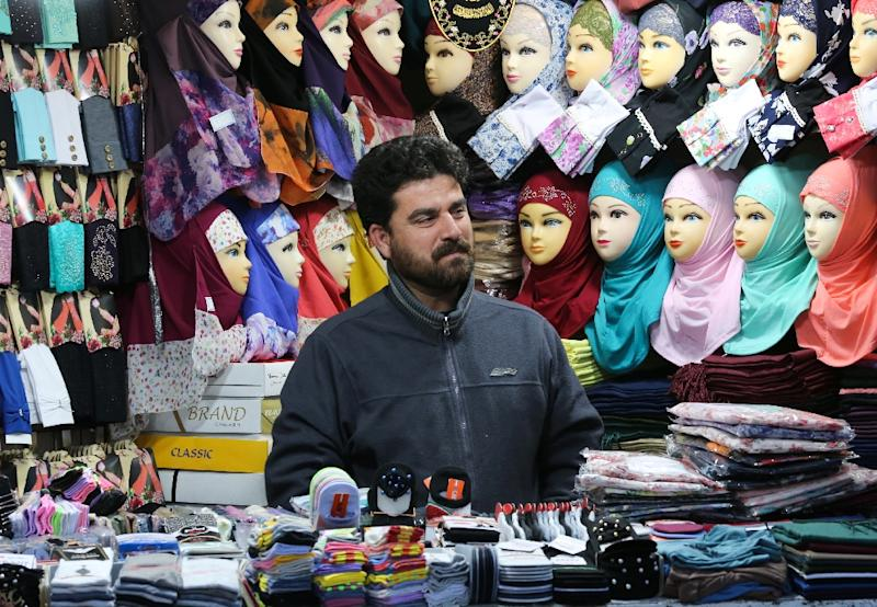 A man stands at his shop in the Shiite holy city of Qom, south of the Iranian capital Tehran, where the Islamic revolution still holds a powerful sway even as once-unthinkable signs of modernity creep into the city (AFP Photo/ATTA KENARE)