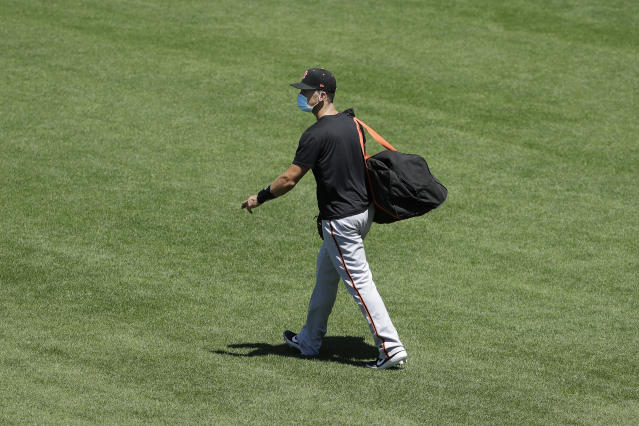 FILE - In this Sunday, July 5, 2020, file photo, San Francisco Giants' Buster Posey carries his bag during a baseball practice in San Francisco. Posey is the latest big-name player to skip this season because of concerns over the coronavirus pandemic. Posey announced his decision on Friday, July 10, 2020. He says his family finalized the adoption of identical twin girls this week. The babies were born prematurely and Posey said after consultations with his wife and doctor he decided to opt out of the season. (AP Photo/Jeff Chiu, File)
