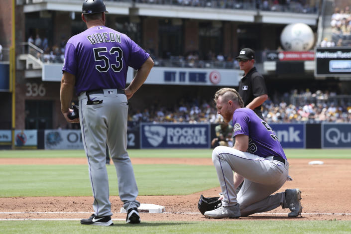 Colorado Rockies' Jon Gray, right, kneels at first base after a collision with San Diego Padres starting pitcher Ryan Weathers as Ronnie Gideon looks on in the third inning of a baseball game Sunday, July 11, 2021, in San Diego. (AP Photo/Derrick Tuskan)