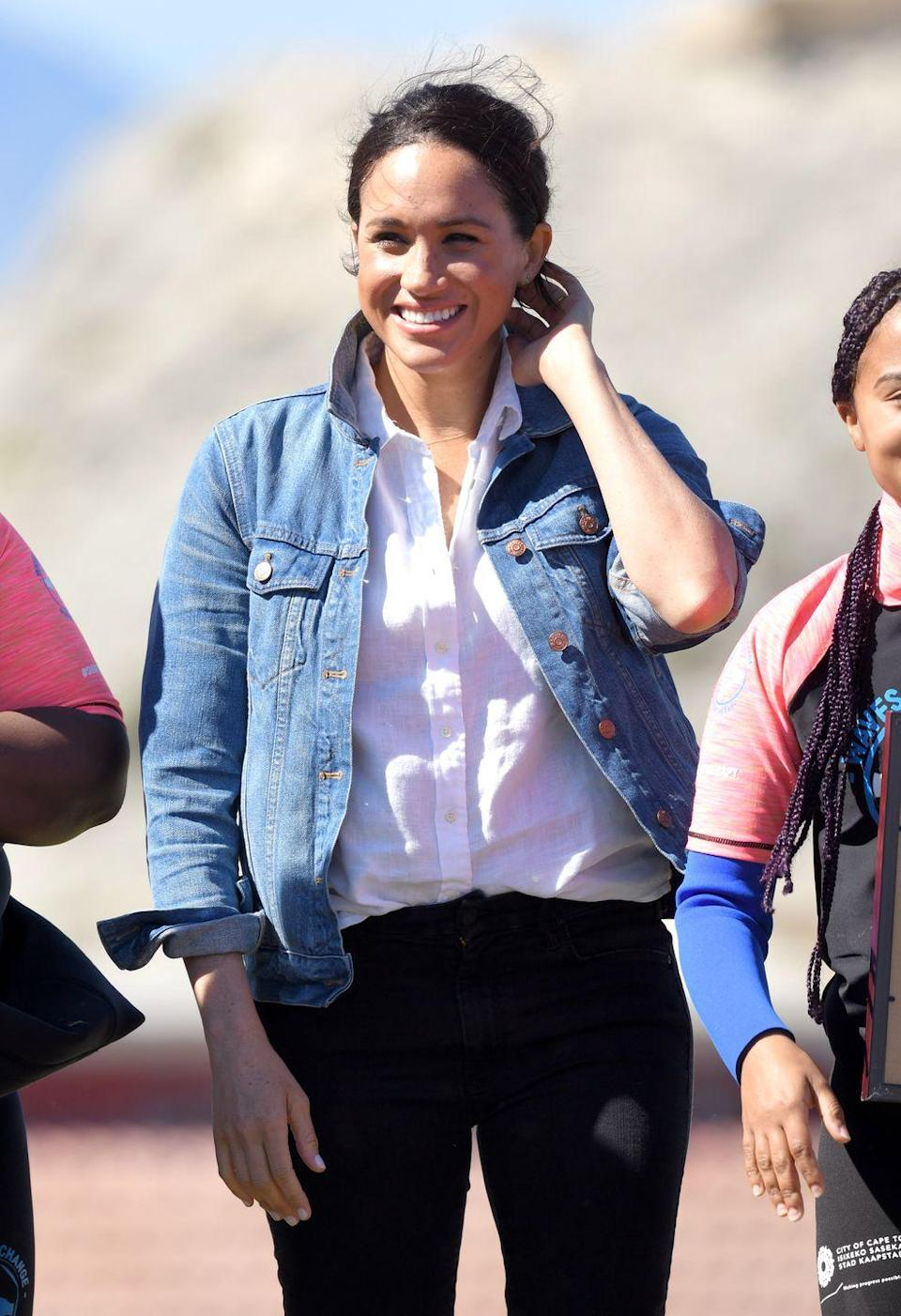 """<p>The Duchess of Sussex went for a classic option while visiting Monwabisi Beach in South Africa. She sported a simple white linen J. Crew shirt for the outing. </p><p><a class=""""link rapid-noclick-resp"""" href=""""https://go.redirectingat.com?id=74968X1596630&url=https%3A%2F%2Fwww.jcrew.com%2Fp%2Fwomens_category%2Fshirts_tops%2Frelaxedfit-baird-mcnutt-irish-linen-shirt%2FAW700%3Fcolor_name%3Dwhite&sref=https%3A%2F%2Fwww.elle.com%2Ffashion%2Fshopping%2Fg36477134%2Fmeghan-markle-white-button-down-shirts%2F"""" rel=""""nofollow noopener"""" target=""""_blank"""" data-ylk=""""slk:Shop Now"""">Shop Now</a></p>"""