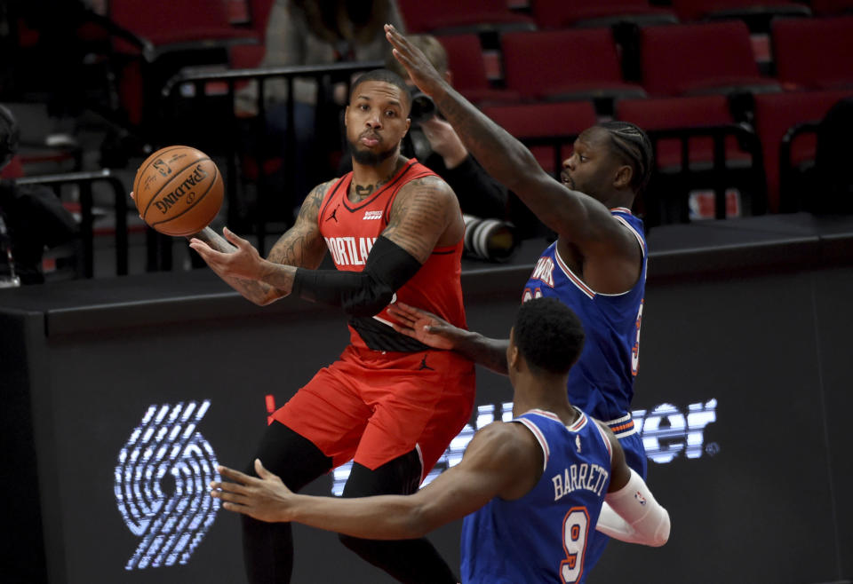 Portland Trail Blazers guard Damian Lillard left, passes the ball on New York Knicks guard RJ Barrett center, and forward Julius Randle, right, during the first quarter of an NBA basketball game in Portland, Ore., Sunday, Jan. 24, 2021. (AP Photo/Steve Dykes)