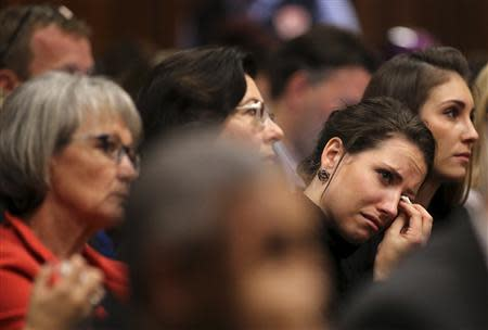 Aimee Pistorius, sister of South African Olympic and Paralympic sprinter Oscar Pistorius, reacts during her brother's trial at the North Gauteng High Court in Pretoria April 9, 2014. REUTERS/Siphiwe Sibeko/Pool