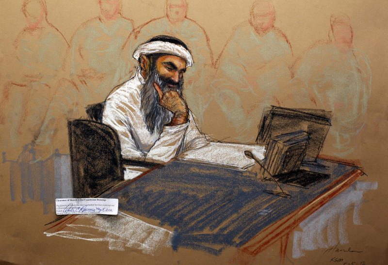 In this photo of a sketch by courtroom artist Janet Hamlin and reviewed by the U.S. Department of Defense, Khalid Sheikh Mohammed reads a document during his military hearing at the Guantanamo Bay U.S. Naval Base in Cuba, Saturday, May 5, 2012. The self-proclaimed mastermind of the Sept. 11 attacks, Khalid Sheikh Mohammed repeatedly declined to respond to a judge's questions Saturday and his co-defendant Walid bin Attash was briefly restrained at a military hearing as five men charged with the worst terror attack in U.S. history appeared in public for the first time in more than three years. (AP Photo/Janet Hamlin, Pool)