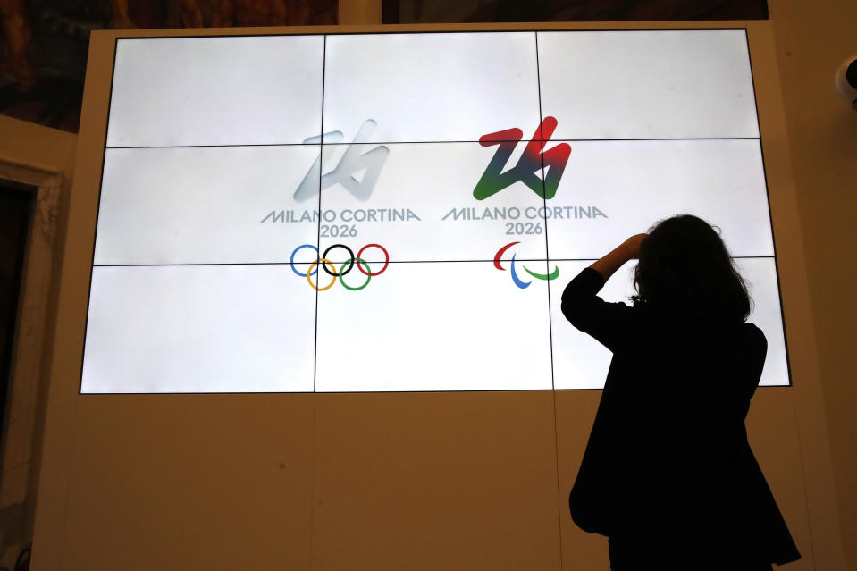 """The logo of 2026 Milan-Cortina Olympics and Paralympics, right, are unveiled to the journalists at a press conference in Rome, Tuesday, March 30, 2021. A futuristic white-on-white logo was unveiled as the emblem for the 2026 Milan-Cortina Olympics on Tuesday following an online vote. Nearly a million votes were cast, 871,566 to be exact, over the last two weeks from Italy and 168 other nations for the two finalists. The """"Futura"""" logo received 75 percent of the votes, winning easily ahead of the more traditional """"Dado"""" option. (AP Photo/Alessandra Tarantino)"""