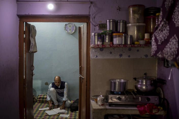 Muhammad Nasir Khan, who was shot by a Hindu mob during the February 2020 communal riots, sifts through his legal and medical files inside his home in North Ghonda, one of the worst riot affected neighborhood, in New Delhi, India, Friday, Feb. 19, 2021. As the first anniversary of bloody communal riots that convulsed the Indian capital approaches, Muslim victims are still shaken and struggling to make sense of their struggle to seek justice. (AP Photo/Altaf Qadri)