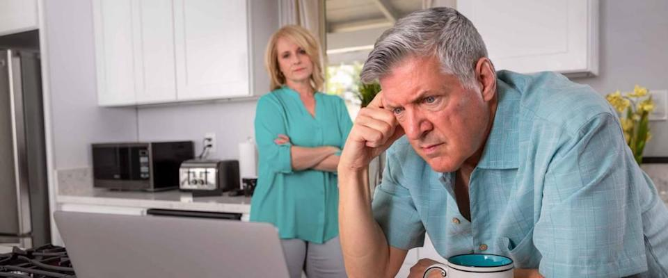 Senior couple in kitchen, looking at laptop and looking stressed