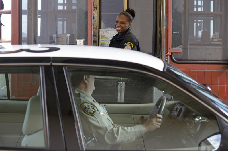 Toll taker Tiffany Hudson talks with a California Highway Patrolman on her last day of work at the Golden Gate Bridge Tuesday, March 26, 2013 in San Francisco. The historic bridge will take a high-tech leap forward when it becomes the first California span to replace all human toll takers with an electronic system that ends the need for motorists to stop and pay cash. Toll takers will collect money for the last time early Wednesday before the toll booths are closed for good. (AP Photo/Eric Risberg)
