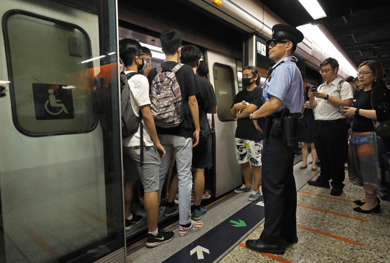 A police officer stands next to some protesters who are blocking the door of a train at a subway platform in Hong Kong on Tuesday, July 30, 2019. Protesters in Hong Kong have disrupted subway service during the morning commute by blocking the doors on trains, preventing them from leaving the stations. (AP Photo/Vincent Yu)
