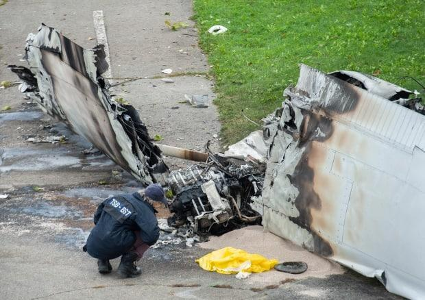 A member of the Transportation Safety Board (TSB) inspects the wreckage of a plane on Sunday at a crash site in Montreal. (Graham Hughes/The Canadian Press - image credit)