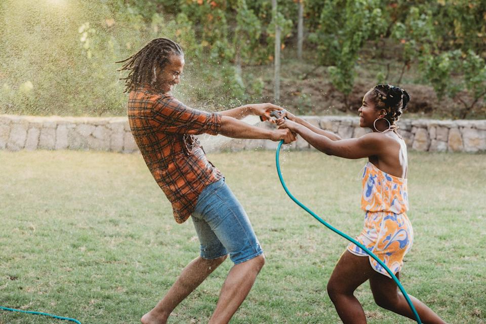 Beautiful young couple playing tug of war with sprinkler hose