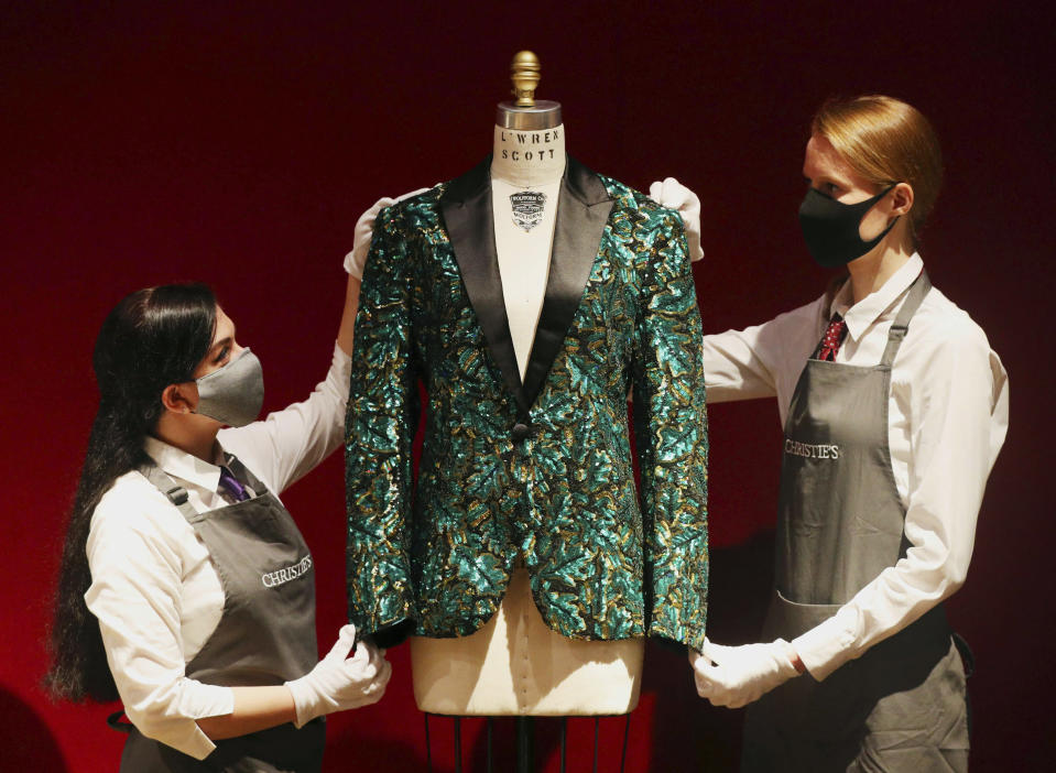 Gallery assistants handle the oak leaf 'Glamouflage' jacket made for Mick Jagger, amongst other items on display at Christie's, from the archive of fashion designer L'Wren Scott before it is offered at auction, in London, Thursday June 10, 2021. (Jonathan Brady/PA via AP)