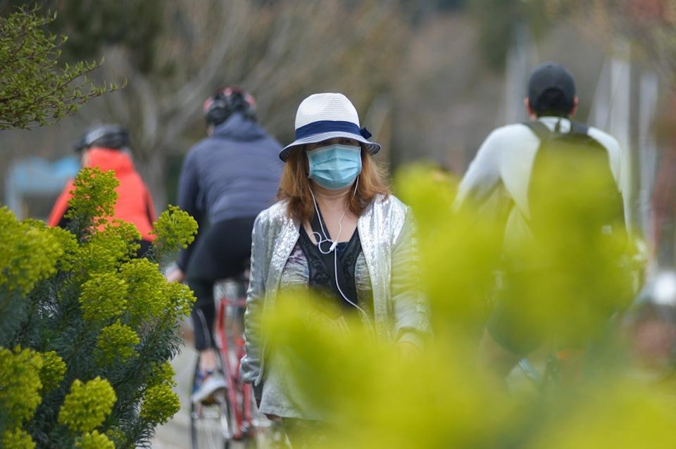 A woman wearing protective face mask is seen walking in the park during COVID-19 virus outbreak