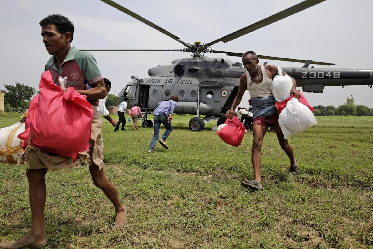 Flood affected people take relief material flown in by the Indian Air Force helicopter on the outskirts of Allahabad, India, Friday, Aug. 26, 2016. Misery eased somewhat, with rains ebbing over the past three days in Uttar Pradesh state, where 200,000 people had moved to relief centers after their homes were submerged, said Deepak Singhal, a state official. Air force helicopters dropped food packets to thousands of people in Allahabad district who preferred to stay on the top floors of their flooded homes and wait for the water to recede rather than move into state-run relief camps. (AP Photo/Rajesh Kumar Singh)