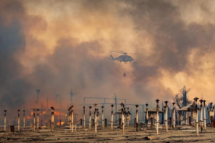 """A helicopter flies above a fire at Le Capannine beach in Catania, Sicily, Italy on July 30.<span class=""""copyright"""">Roberto Viglianisi—Reuters</span>"""