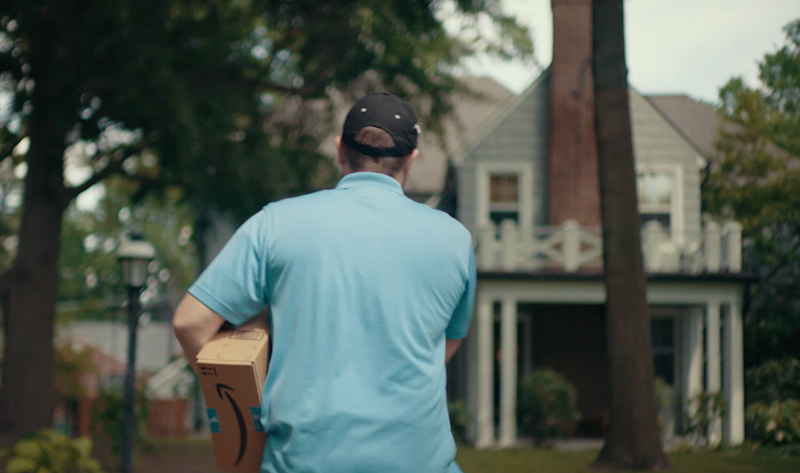 Man carrying an Amazon package walking up to a house.