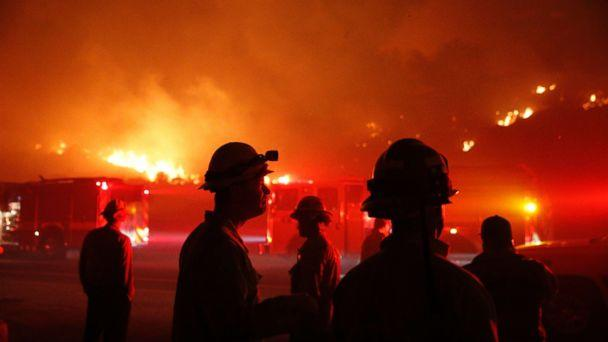 PHOTO: Firefighters gather in front of a residential area as a wildfire burns along the 101 Freeway, Dec. 5, 2017, in Ventura, Calif. (Jae C. Hong/AP)