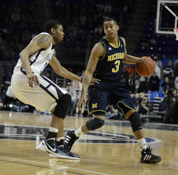 Michigan's Trey Burke (3) looks for room around Penn State's Jermaine Marshall (11) in the second half of NCAA college basketball against Michigan in State College, Pa. on Sunday, March 4, 2012. (AP Photo/Ralph Wilson)