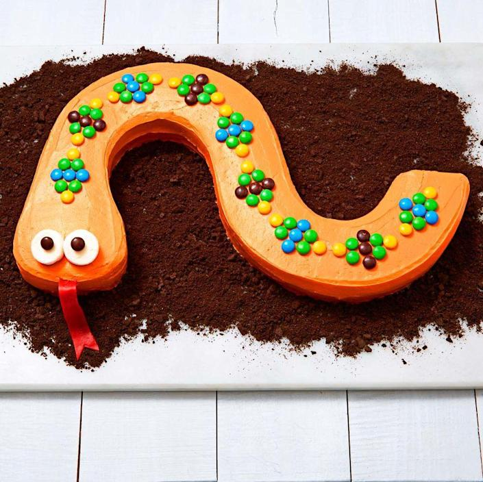 """<p>Marshmallow crispy treats + royal icing + Halloween candy = this delicious dessert!</p><p><a href=""""https://www.womansday.com/food-recipes/food-drinks/recipes/a11984/peanut-chocolate-banana-snakes-recipe-123645/"""" rel=""""nofollow noopener"""" target=""""_blank"""" data-ylk=""""slk:Get the"""" class=""""link rapid-noclick-resp""""><strong><em>Get the </em></strong></a><em><strong><a href=""""https://www.womansday.com/food-recipes/a36831300/snake-cake-recipe/"""" rel=""""nofollow noopener"""" target=""""_blank"""" data-ylk=""""slk:Snake Cake recipe."""" class=""""link rapid-noclick-resp"""">Snake Cake recipe. </a></strong></em></p>"""