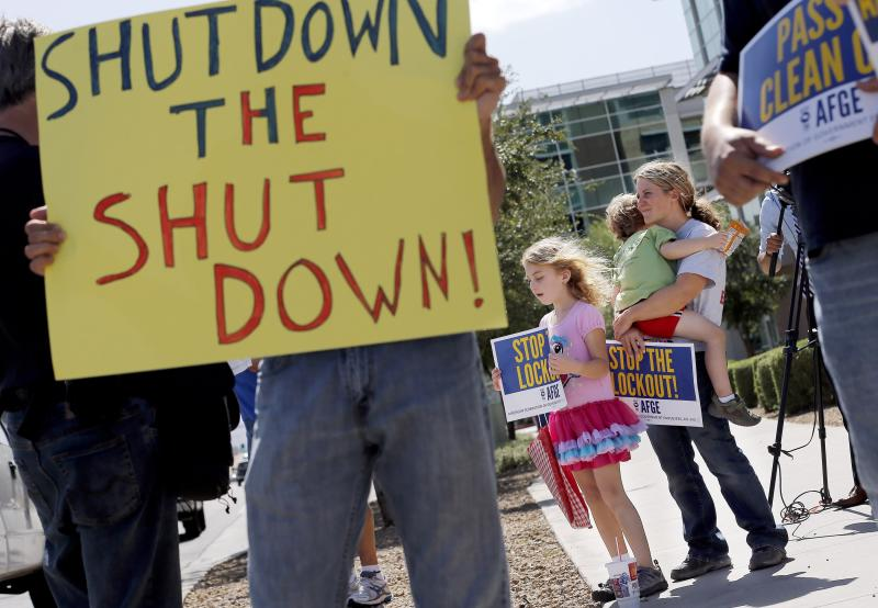 As the federal government shutdown continues, Tory Anderson, right, with her kids Audrey, 7, and Kai, 3, of Goodyear, Ariz., join others as they rally for the Alliance of Retired Americans to end the shutdown in front of the Social Security Administration offices on Wednesday, Oct. 9, 2013, in Phoenix. Other groups rallying to end the government shutdown include Professional Aviation Safety Specialists, the American Federation of Government Employees AFL-CIO, and Arizona FairShare. (AP Photo/Ross D. Franklin)