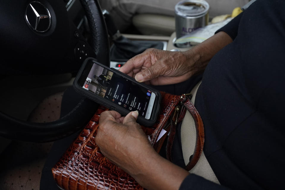 An Anderson United Methodist Church member monitors the First Sunday service live cast on her cellphone Dec. 6, 2020, in Jackson, Miss. The church has taken to using digital means by which to broadcast services to its members. However, the congregants gather in the church's parking lot the first Sunday of each month, since the start of covid protocols, to celebrate the receiving of communion in their private vehicles. (AP Photo/Rogelio V. Solis)