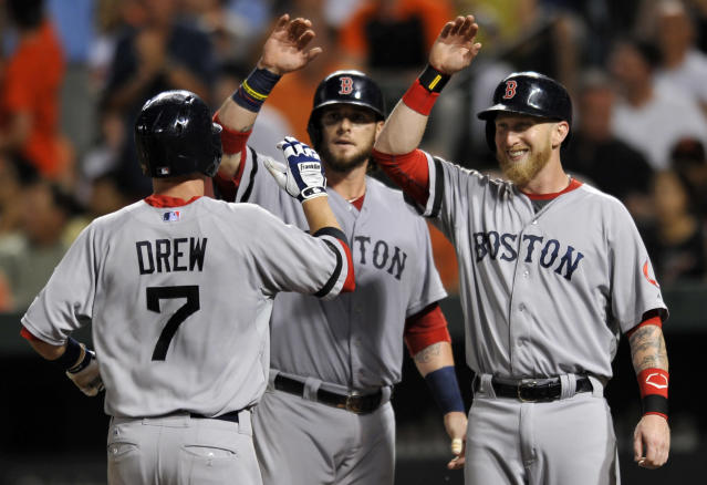 Boston Red Sox Stephen Drew, left, is congratulted by teammates Jarrod Saltalamacchia, center, and Mike Carp after hitting a three-run home run against the Baltimore Orioles in the fourth inning of a baseball game on Saturday, July 27, 2013, in Baltimore. (AP Photo/Gail Burton)