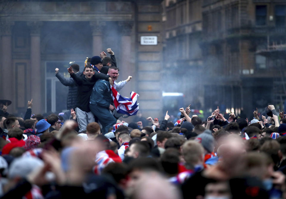 Rangers soccer fans defy pandemic restrictions to celebrate winning the  Scottish Premiership title, at George Square in Glasgow, Scotland, Sunday March 7, 2021.  Rangers took their 55th domestic league title, their first Scottish Premiership title in 10 years, after Celtic failed to beat Dundee United on Sunday.  (Jane Barlow/PA via AP)