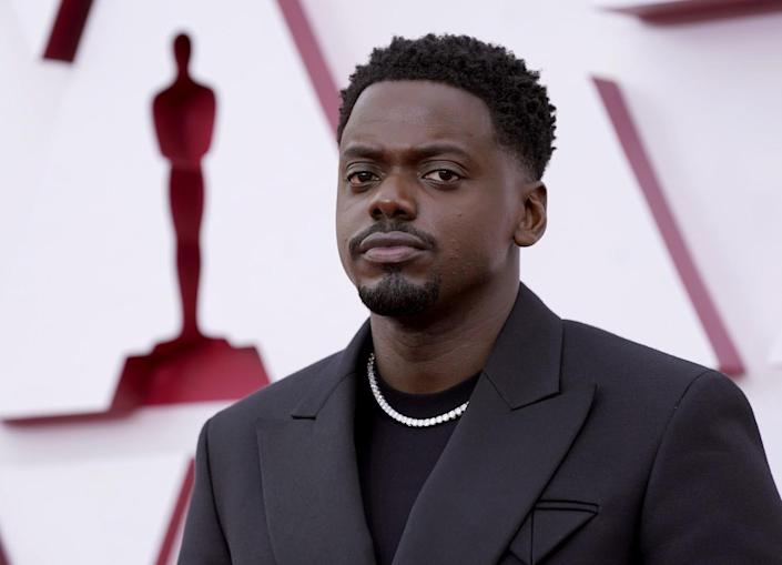 Daniel Kaluuya in a black jacket over a black shirt with a white necklace