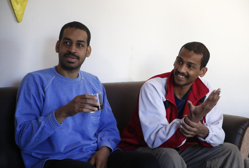 """FILE - In this March 30, 2018, file photo, Alexanda Amon Kotey, left, and El Shafee Elsheikh, who were allegedly among four British jihadis who made up a brutal Islamic State cell dubbed """"The Beatles,"""" speak during an interview with The Associated Press at a security center in Kobani, Syria. The men said that their home country's revoking of their citizenship denies them a fair trial. """"The Beatles"""" terror cell is believed to have captured, tortured and killed hostages including American, British and Japanese journalists and aid workers. (AP Photo/Hussein Malla, File)"""