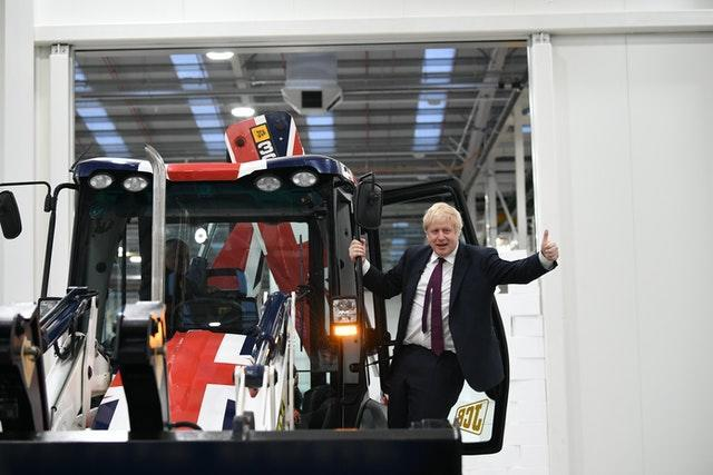 Prime Minister Boris Johnson gestures after driving a Union flag-themed JCB, with the words Get Brexit Done (Stefan Rousseau/PA)