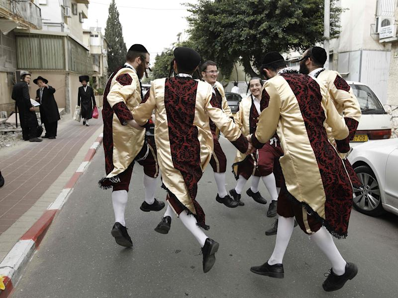 Ultra-Orthodox Jewish men wearing costumes dance on a street in the central Israeli city of Bnei Brak: AFP/Getty