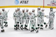 Dallas Stars' John Klingberg (3) celebrates with goaltender Jake Oettinger (29) and others after their team's 5-2 win against the Detroit Red Wings in an NHL hockey game in Dallas, Tuesday, April 20, 2021. (AP Photo/Tony Gutierrez)