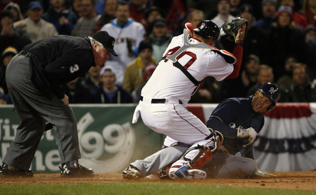 Boston Red Sox catcher A.J. Pierzynski (40) holds up the ball after tagging out Milwaukee Brewers' Carlos Gomez, right, as umpire Tim Welke, left, watches during the fourth inning of a baseball game at Fenway Park in Boston, Saturday, April 5, 2014. (AP Photo/Winslow Townson)