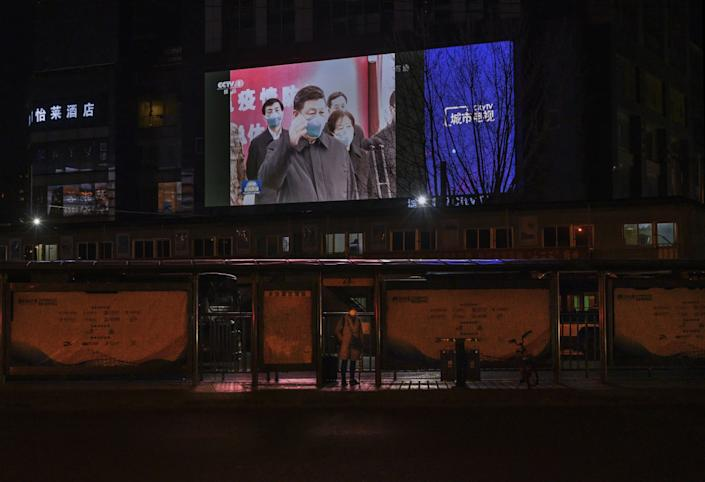 A TV screen shows images of President Xi Jinping visiting Wuhan, China, on March 10, 2020.