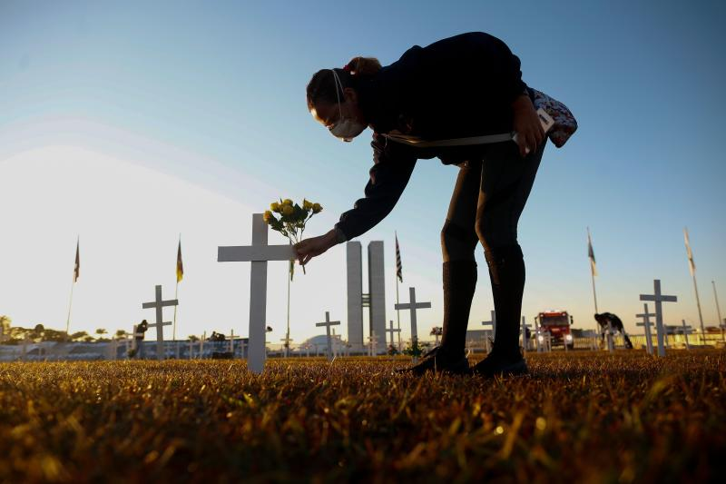 A demonstrator places flowers on a cross during a protest against Brazilian President Jair Bolsonaro and in honour of the people who died of COVID-19 in which 1000 crosses were placed in front of the National Congress in Brasilia, on June 28, 2020, amid the novel coronavirus pandemic. - The pandemic has killed at least 495,288 people worldwide, including more than 55,000 in Brazil, since it surfaced in China late last year, according to an AFP tally at 1900 GMT on Saturday, based on official sources. (Photo by Sergio LIMA / AFP) (Photo by SERGIO LIMA/AFP via Getty Images)