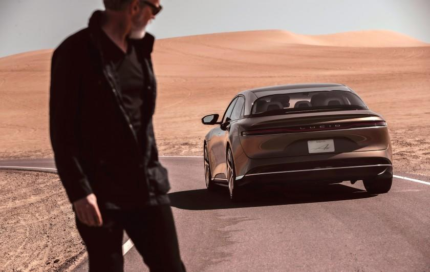 An unidentified man in a flat desert scene looks at a Lucid Air electric car in a 2020 promotional photograph.