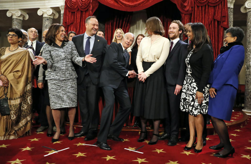 FILE - In this Jan. 3, 2017, file photo, then-Vice President Joe Biden, center, ducks down so all of the family of then-Sen. Kamala Harris, D-Calif., second from right, can be seen for a group photo during a mock swearing in ceremony in the Old Senate Chamber on Capitol Hill in Washington. (AP Photo/Alex Brandon, File)